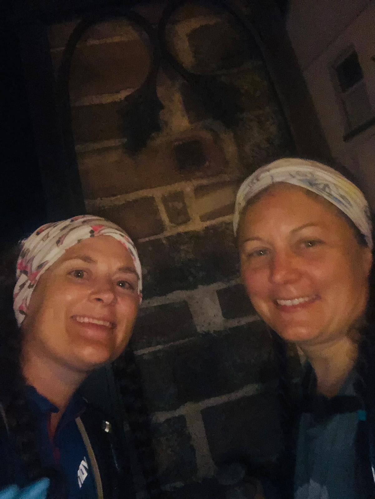 A grainy night photo of Sarah and Ellen at the pillar in Frodsham